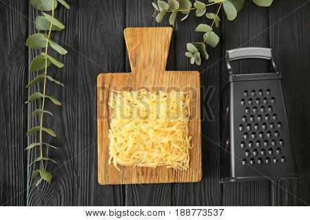 Grater and wooden board with cheese on table