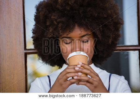 Close up of woman with frizzy hair drinking coffee against door