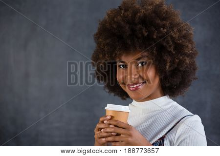 Portrait of smiling woman holding disposable coffee cup against wall
