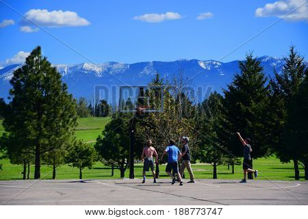 KALISPELL, MONTANA, USA - May 9, 2017: College students at Flathead Valley Community College playing a pick up game of basketball on campus.
