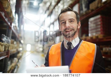 Wholesale distributor looking at camera inside storehouse