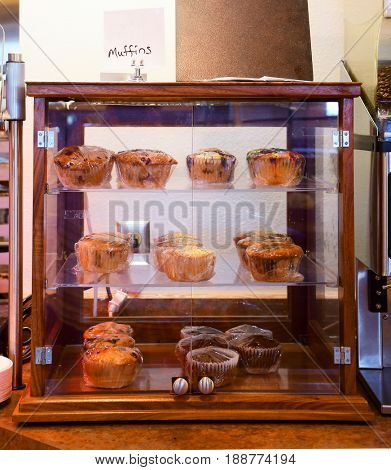 Variety of muffins in a glass display case at a cafeteria