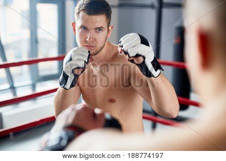 Kick-boxer in gloves attacking his rival