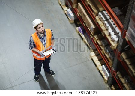 Supervisor with touchpad looking at goods on shelf