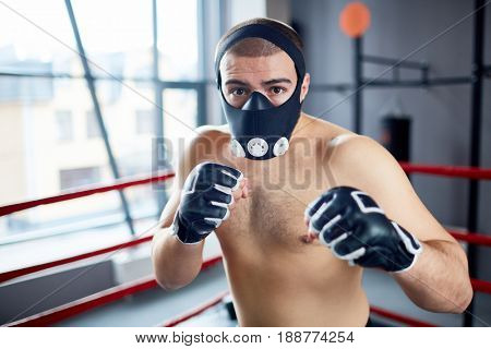 Strong kick-boxer in protective mask looking at his rival during attack