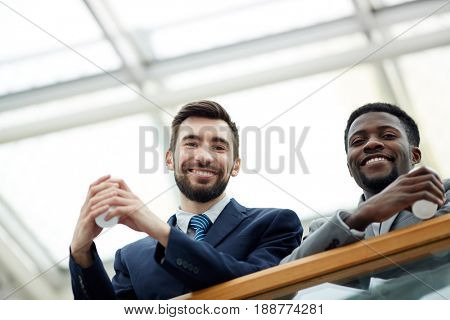 Low angle portrait of handsome bearded businessman with African-American colleague looking down from glass balcony and smiling holding cups during break