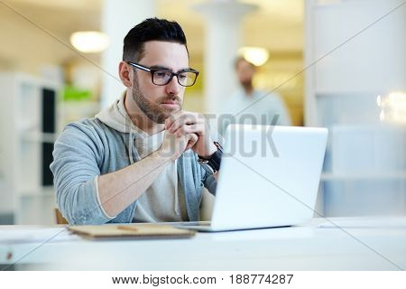 Portrait of modern handsome businessman wearing casual clothes and glasses busy working with laptop in modern office, looking troubled