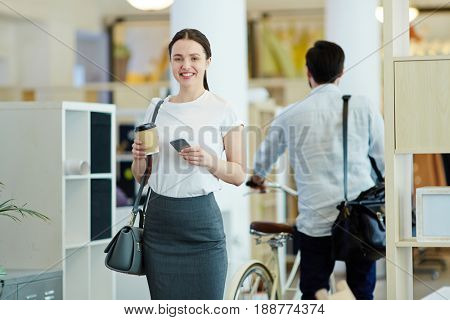 Portrait of happy young woman going home from work in office, holding smartphone and disposable coffee cup