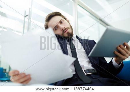 Busy economist with touchpad looking through papers and talking on cellphone in office