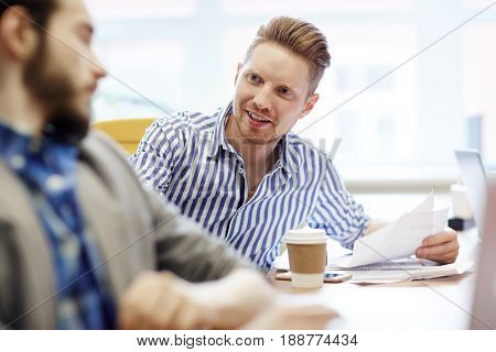 Two professional economists having discussion at meeting