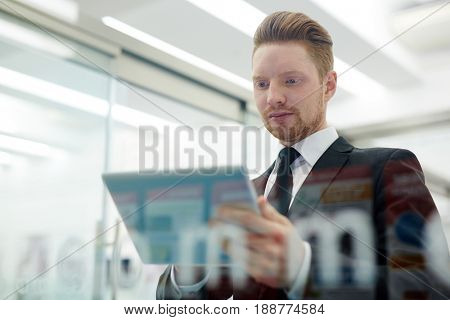 Serious businessman with touchpad watching through online information