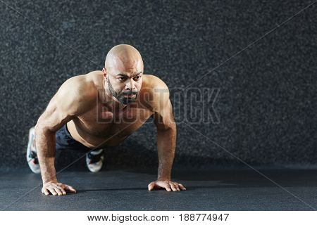 Young muscular man doing push-ups on the floor