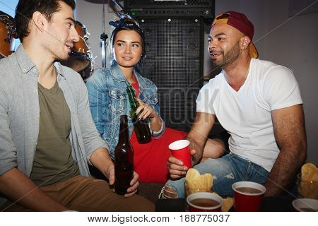 Small group of intercultural friends having beer in club