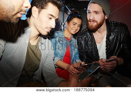 Young buddies with gadgets spending time in club