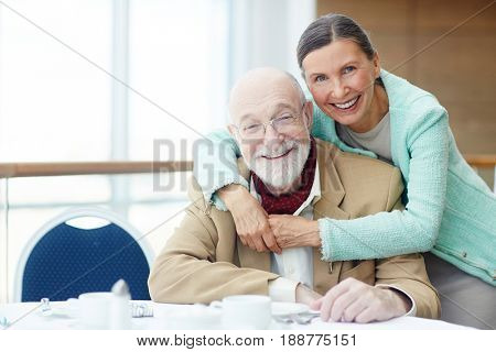 Amorous seniors sitting by served table in cafe or restaurant