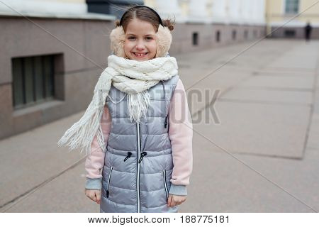 Little girl in down-jacket looking at camera outdoors