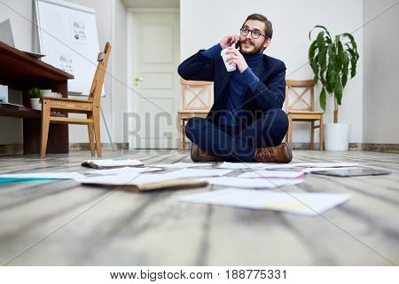 Portrait of modern bearded man speaking by phone and sorting documents sitting on floor in office  with coffee cup