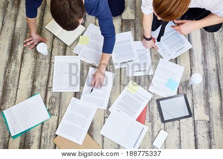 Top view of assorted documents and contracts laid out on wooden office floor with two unrecognizable  people working