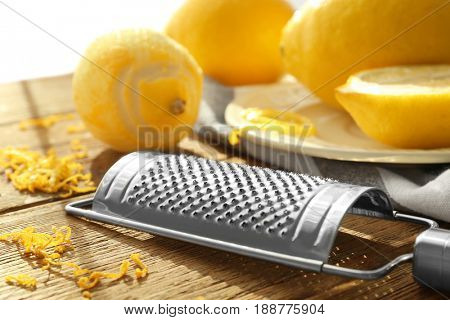 Grater and lemons on wooden table, closeup