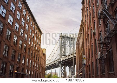 Manhattan Bridge between Manhattan and Brooklyn over East River seen from a narrow alley enclosed by two brick buildings on a sunny day, New York City