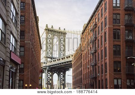 famous Manhattan Bridge between Manhattan and Brooklyn over East River seen from a narrow alley enclosed by two brick buildings on a sunny day, New York City