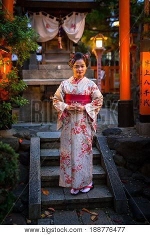 KYOTO, JAPAN - NOVEMBER 10, 2016: Young woman wearing traditional japanese kimono walks on the street of Gion, Kyoto old town, Japan. Kimono is a Japanese traditional garment.