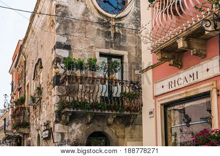 TAORMINA, SICILY, ITALY - APRIL 27, 2017: Historic architecture detail in Taormina, Sicily, Italy with a view of old stone townhouses with wrought iron balconies and a red wall in the foreground