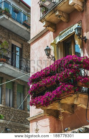 TAORMINA, SICILY, ITALY - APRIL 27, 2017: Trattoria or restaurant balcony with purple petunias in rows forming an eye catching display from the street below in Castelmola, Sicily Italy