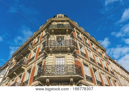 STRASSBOURG, FRANCE- CIRCA MARCH, 2017: Corner angle of a historic townhouse with ornate wrought iron balconies and brick and stone architecture in Strasbourg, Alsace, France