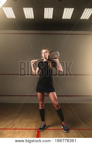 Woman with squash racket, indoor training club