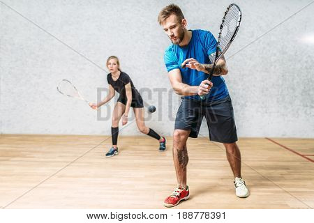 Couple with squash rackets, indoor training club