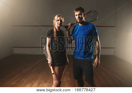 Male and female squash game players with rackets