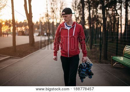 Young man with roller skates in hands