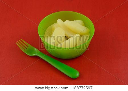 Canned Bartlett pear slices in green plastic bowl with plastic fork on red wood table