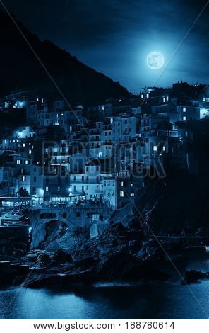 Manarola overlook Mediterranean Sea and moonrise with buildings over cliff in Cinque Terre at night, Italy.