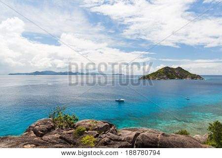 travel, landscape and nature concept - island and boats in indian ocean on seychelles