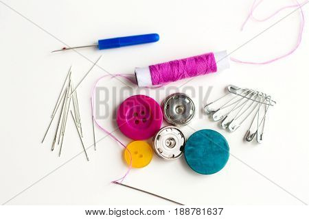 needlework and tailoring concept - sewing buttons, needles, pins and thread spool