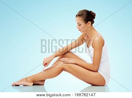 people, beauty and hair removal concept - beautiful woman with safety razor shaving legs sitting on floor over blue background
