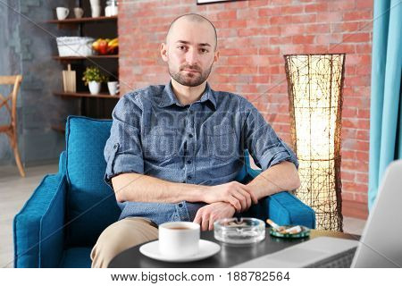 Handsome man smoking cigarette at home