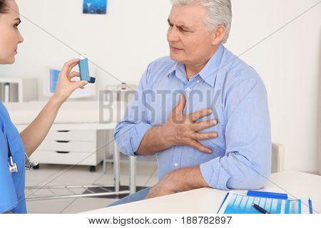 Doctor giving elderly man inhaler in clinic