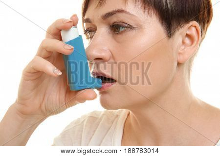 Adult woman using inhaler on white background