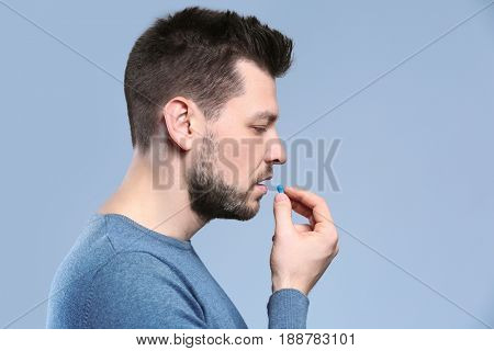Handsome young man taking pill on color background