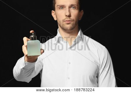 Handsome man using perfume on black background