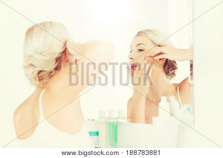 beauty, hygiene, skin problem and people concept - young woman looking to mirror and squeezing pimple at home bathroom