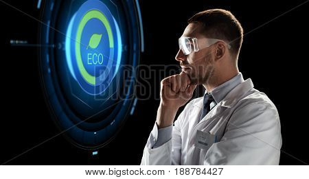 ecology, science, and people concept - male doctor or scientist in white coat and safety glasses looking at virtual projection with eco icon over black background