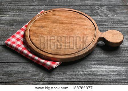 Round cutting board on wooden background
