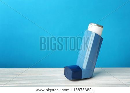 Asthma inhaler on blue background