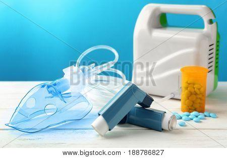 Asthma inhalers, nebuliser and pills on blue background