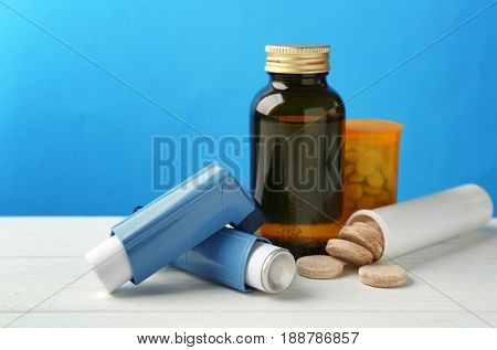 Asthma inhalers with medicines on blue background