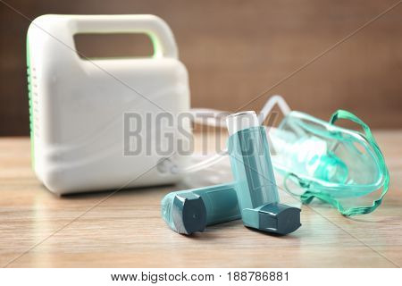 Asthma inhalers and nebuliser on wooden table